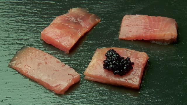 "caviar garnish added to bite of smoked salmon hor d""oeavre - garnish stock videos & royalty-free footage"
