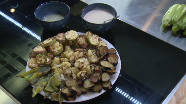 cawliflower. handheld view of a plate of baked cawliflower florets decorated with fried zucchini and green peppers on a kitchen counter. - garlic stock videos & royalty-free footage