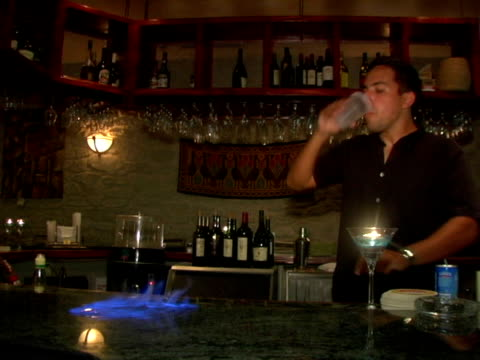 ms, cayman islands, grand cayman, man pouring vodka on granite bar counter and lit it on fire - 若い男性だけ点の映像素材/bロール