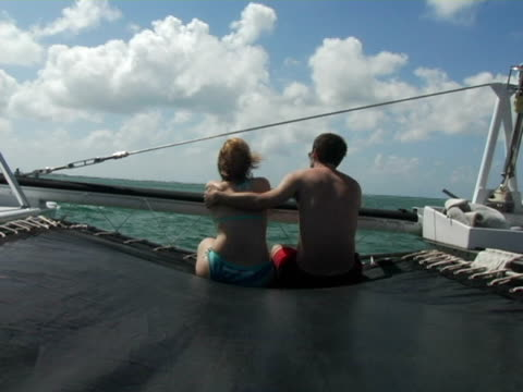 stockvideo's en b-roll-footage met ms, cayman islands, grand cayman, stingray city, young couple sitting in front of catamaran in sea, rear view - zij aan zij