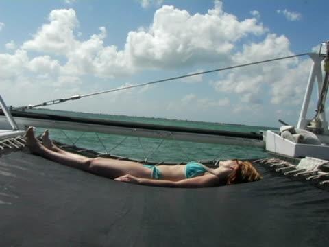 vidéos et rushes de ms, cayman islands, grand cayman, stingray city, young woman sun tanning on catamaran in sea - seulement des jeunes femmes