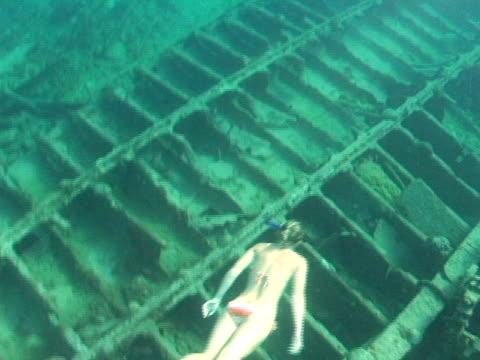 vidéos et rushes de ms, cayman islands, grand cayman, woman swimming above ship wreck - seulement des jeunes femmes
