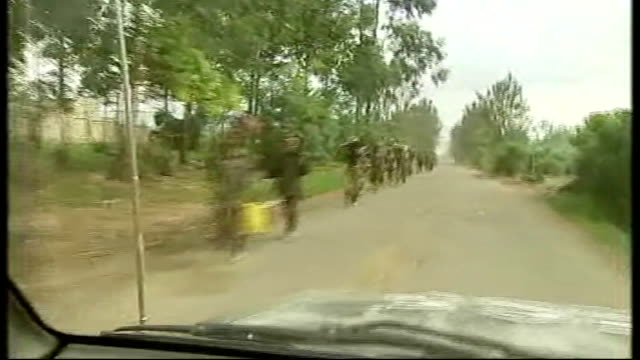 Ceasefire between government and rebel army breaking down INT CAR Long line of Nkunda rebel soldiers towards past TRACKING SHOT USAID truck along...