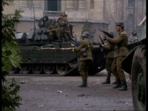vídeos y material grabado en eventos de stock de ceausecus executed; itn lib side soldiers stand beside tanks firing rifles - rumania