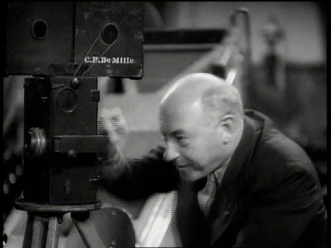 vidéos et rushes de cecil b. demille cranking old pathe camera while smiling and talking / hollywood, california, united states - thème de la photographie