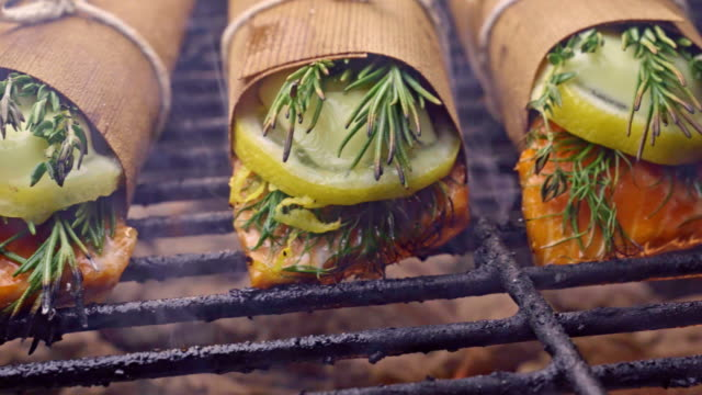 vídeos de stock e filmes b-roll de cedar plank salmon with lemon and herbs and bacon wrapped asparagus - marisco