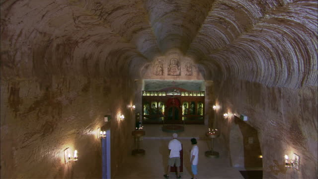 ws td ha ceiling and altar in of underground russian orthodox church, worshippers lighting candles, coober pedy, south australia, australia - votive candle stock videos and b-roll footage