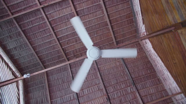ceiling fan cooling in a tropical island thatched roof hotel resort. - ceiling fan stock videos & royalty-free footage