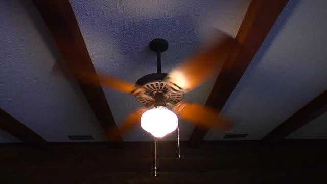 vídeos de stock, filmes e b-roll de a ceiling fan spins. - ventilador de teto