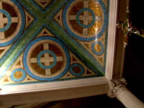ceiling w/ geometric shapes in several colors to golden crucifix cross unlit candles on top of pedestal wall w/ painting of people bg christian... - sockel stock-videos und b-roll-filmmaterial