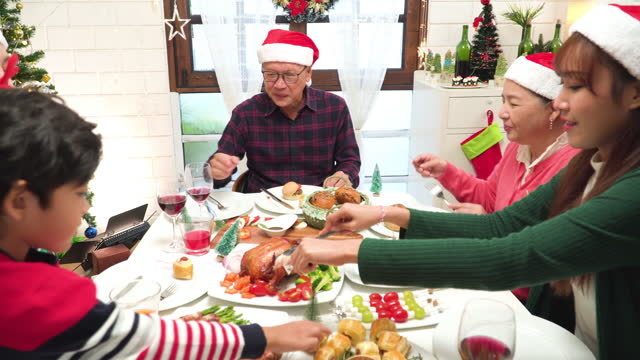 celebrate christmas moment of southeast asian multi-generation family, grandfather, grandmother, father, mother and daughter, son at dinner table with christmas full course food, grilled chicken, green, red food in a decorated home with tree and ornament. - 65 69 years stock videos & royalty-free footage