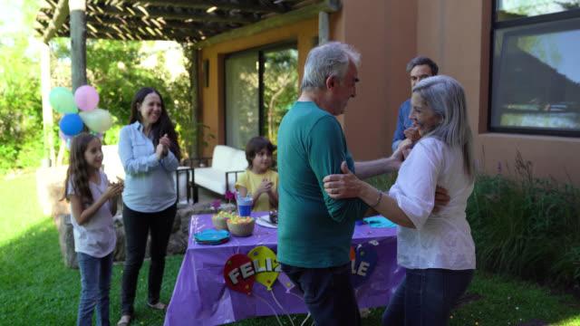 家族が彼らの周りに拍手と歓声を上げながら、先輩の妻と踊る別の年を祝う - 夫点の映像素材/bロール