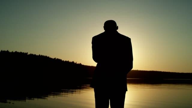 Celebrating success. Businessman admiring lake sunset