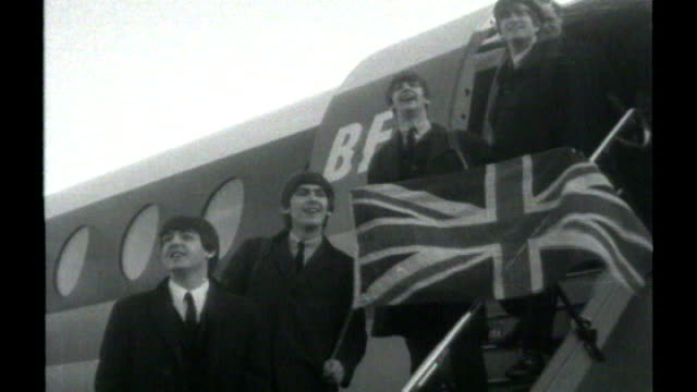 celebration of 50 years of modern british culture; 34085 / london: beatles pose with union jack flag on steps of plane after returning from paris... - bandiera del regno unito video stock e b–roll