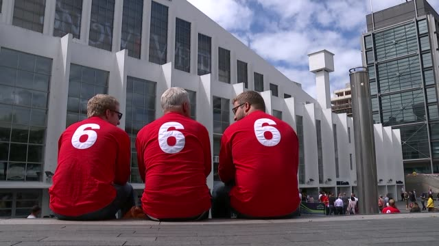celebrations for 50 year anniversary of england world cup win in 1966; back view men sitting wearing 6 t-shirts people entering wembley arena - wembley arena stock videos & royalty-free footage