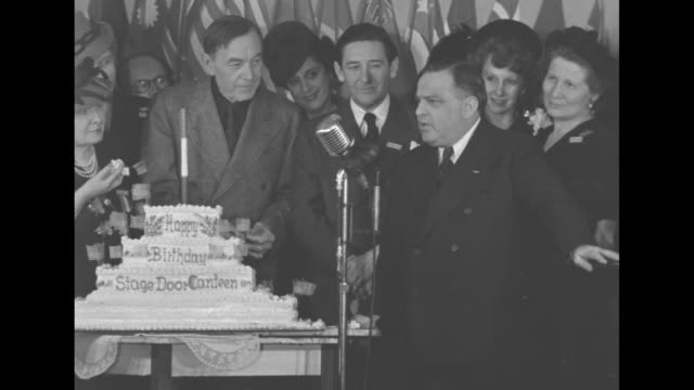 celebrities and dignitaries including harry carey stand behind big birthday cake listening to mayor of new york city fiorello h laguardia speak... - fiorello la guardia stock videos & royalty-free footage