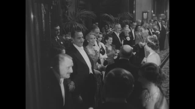vídeos de stock e filmes b-roll de celebrities applaud as elizabeth ii enters lobby of empire theatre for the annual motion picture show for the royal family / woman curtsies for... - kirk douglas actor