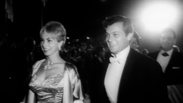vídeos de stock e filmes b-roll de celebrities arriving at 33rd annual academy awards ceremony to honor the best in film for 1960 / exterior of santa monica civic auditorium showing... - 1961