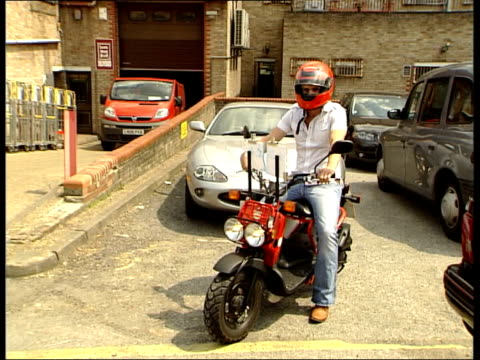 celebrities attending black taxi driver class / janet street porter driving cab brazier onto scooter puts on helmet drives away on scooter pan /... - janet street porter video stock e b–roll