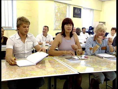 celebrities attending black taxi driver class / janet street porter driving cab thatcher seated chatting to other pupil at desk with map of london... - janet street porter video stock e b–roll