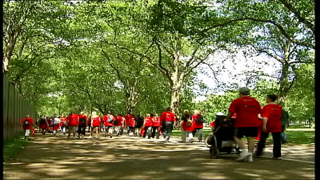 celebrities take part in charity walk to raise money for crohn's disease suffers; itn england: london: hyde park: ext walkers standing under barrier... - itv london tonight weekend stock videos & royalty-free footage