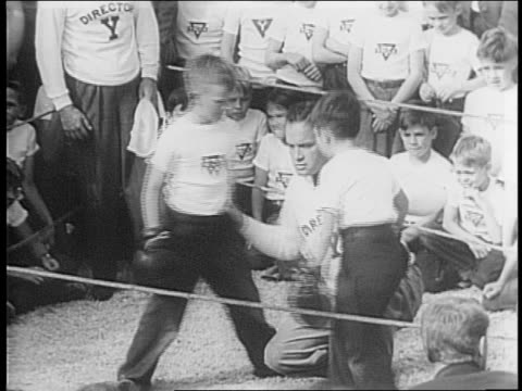 celebrity bob hope volunteers to referee in a kids boxing match /hope puts on a sweater and signs autographs/ children sit on fence cheering/mrs hope... - ボブ ホープ点の映像素材/bロール