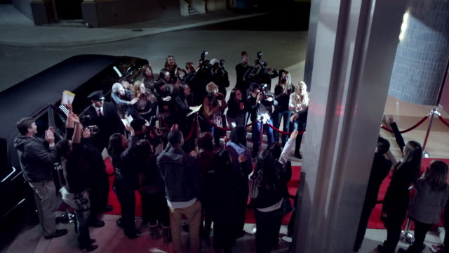 Celebrity couple leaving world premiere walk down red carpet to limousine at awards show
