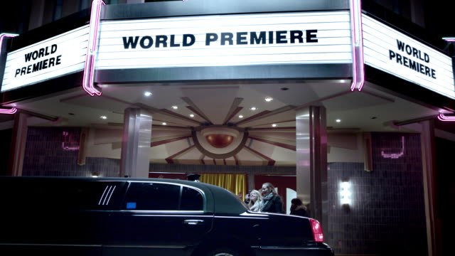 Celebrity couple step out of limousine and walk red carpet under world premiere marquee at awards show