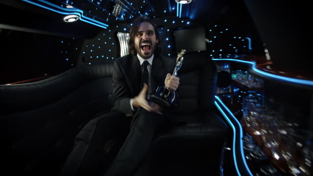 Celebrity in limousine shows off awards trophy and cheers at camera at awards show