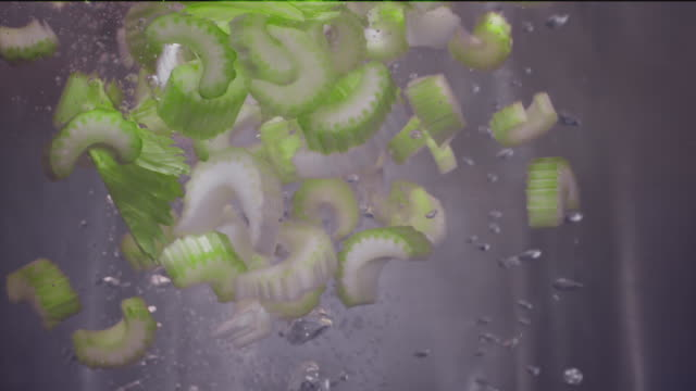 celery falling into boiling water super slow motion 1000 fps - celery stock videos & royalty-free footage