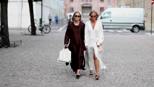 Celine Aagaard wearing white silk dress and Guri Heli wearing brown silk dress seen outside Cathrine Hammel during Oslo Runway SS19 on August 14 2018...