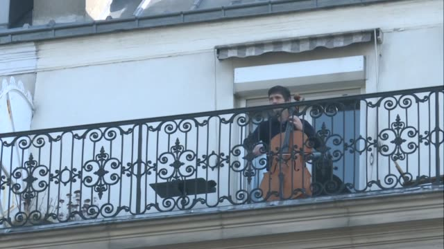 cellist camilo peralta performs for his neighbours on his balcony in paris on the 12th day of lockdown - music stock videos & royalty-free footage
