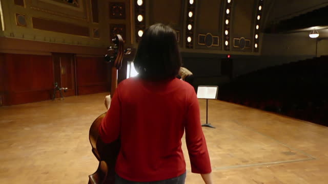 ms ts cellist walking on stage in empty concert hall to perform solo piece / ann arbor, michigan, united states - solo performance stock videos and b-roll footage