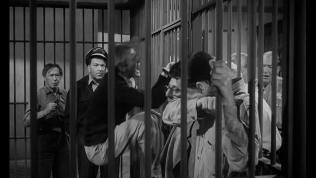 1955 a cellmate suffers from withdrawals while man (frank sinatra) watches - porta della cella video stock e b–roll