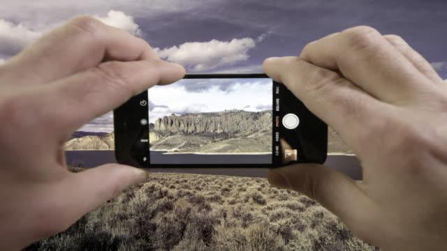 vídeos de stock, filmes e b-roll de cellphone taking video of rocky mountain lake - gunnison
