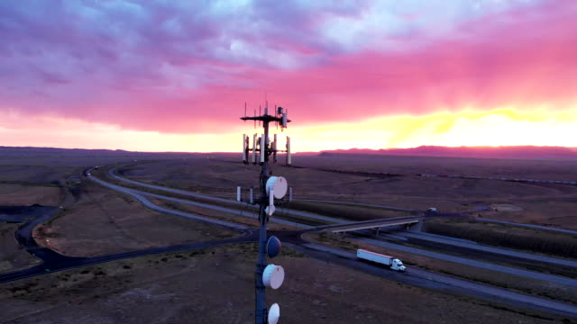 5g cellular tower in the vast and arid desolate desert in eastern utah near moab at dusk under a dramatic cloudscape - telecommunications equipment stock videos & royalty-free footage