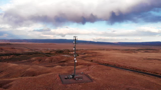 5g cellular tower in the vast and arid desolate desert in eastern utah near moab at dusk under a dramatic cloudscape - tower stock videos & royalty-free footage