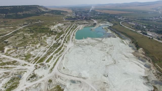 aerial: cement factory near open pit limestone - limestone stock videos and b-roll footage