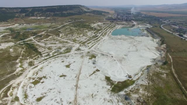 AERIAL: Cement factory near open pit limestone