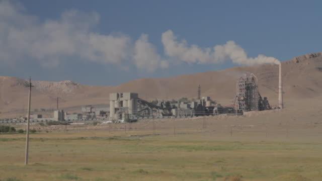 vídeos y material grabado en eventos de stock de cement factory on the green field wide shot - cemento