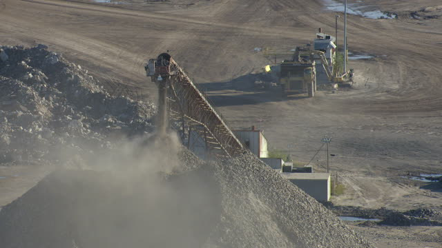 ws aerial pov cement pouring from limestone elevator machine at cement factory / alpena, michigan, united states - 建設機械点の映像素材/bロール