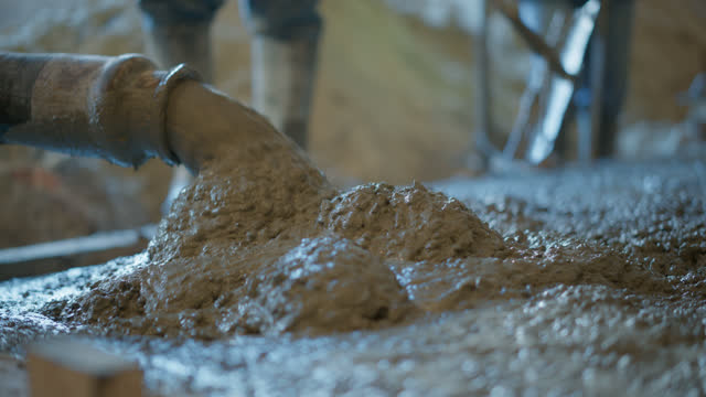 cu cement pours out as a construction worker mixes it at a construction site - cement stock videos & royalty-free footage