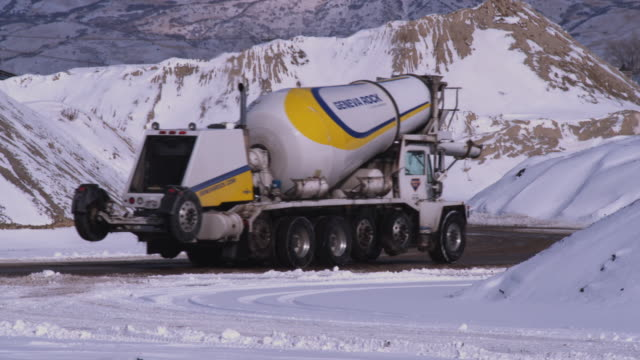 ws cement truck on winding road crossing snow covered wasatch range / provo, utah, usa - provo stock-videos und b-roll-filmmaterial