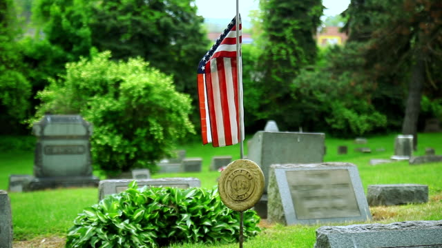 Cemetery gravestones landscape with USA flag close up