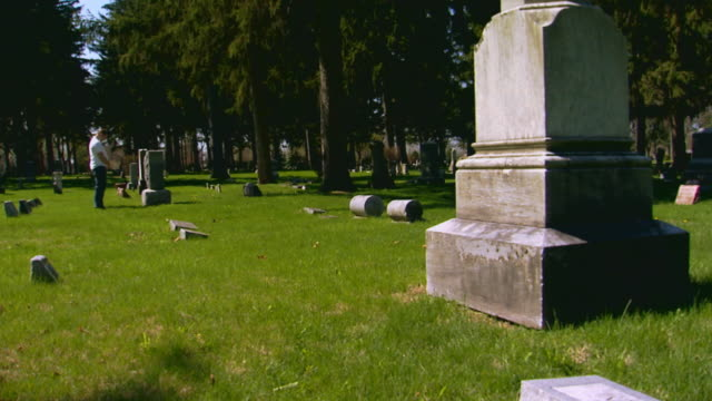 Cemetery monuments, grave stones, man visiting deceased