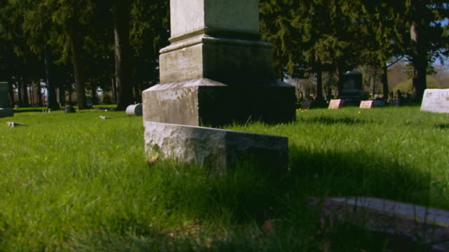 Cemetery monuments, grave stones, man visiting grave