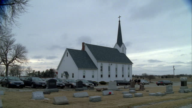 a cemetery surrounds a small country church where a funeral is being held. - funeral stock videos & royalty-free footage