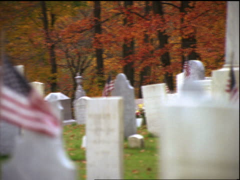 PAN of cemetery with American flags in Autumn / rack focus to flag in foreground / Vermont