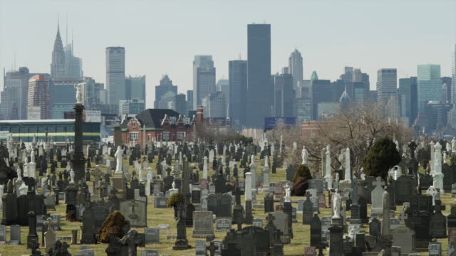 ws pan cemetery with skyline in background / queens,new york city,new york,usa - cemetery stock videos & royalty-free footage