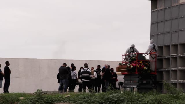 cemetery workers in protective suits use a lift to carry out a wall crypt burial as family members attend the burial at the caju cemetery amidst the... - crypt stock videos & royalty-free footage